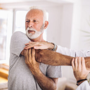 An image of a man with his arm over his chest at the chiropractor